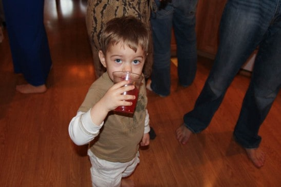A small child drinking juice