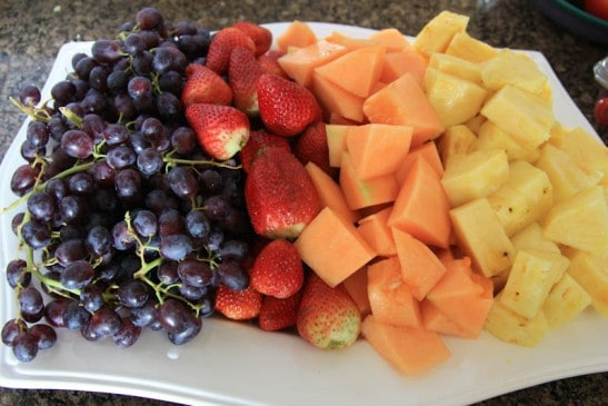 A plate with fruit: grapes, strawberries, cantaloupe and pineapple