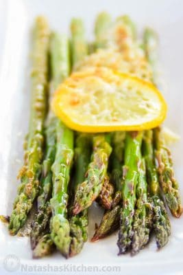 Baked asparagus with lemon, butter and parmesan on a plate garnished with a lemon slice
