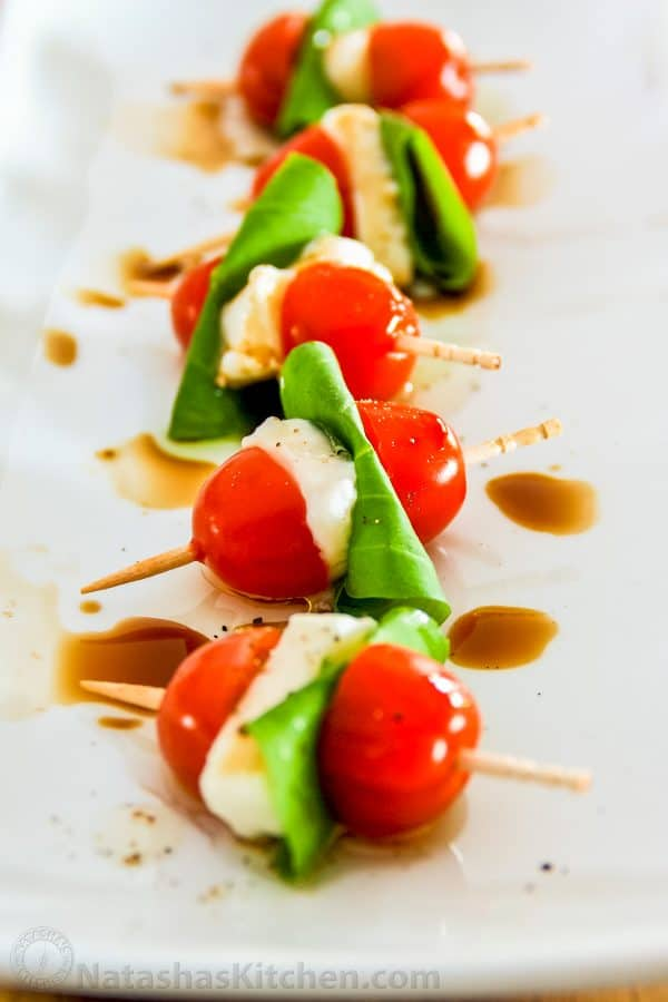 A close up of Caprese salad skewers on a long plate