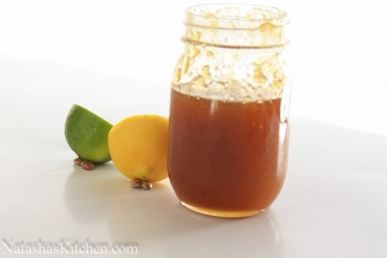 A jar of honey and half a lemon and lime