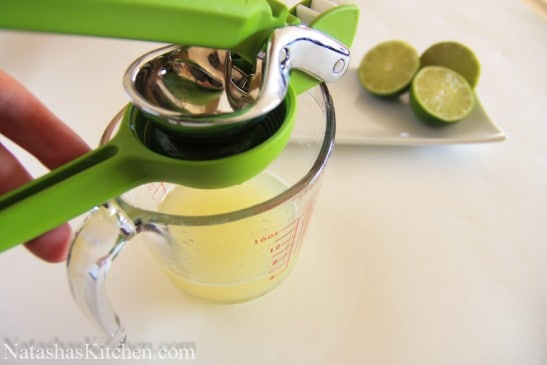 A lime being juiced into a measuring cup