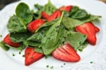 A white plate with strawberry spinach salad