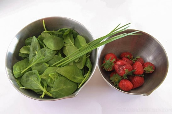 Two bowls one of spinach and green onion and one of strawberries
