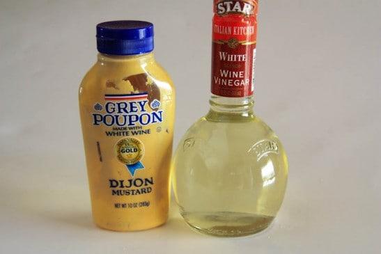 Two bottles one of dijon mustard and one of white wine vinegar