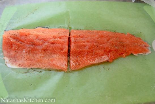 A piece of seasoned trout on a cutting board cut in half