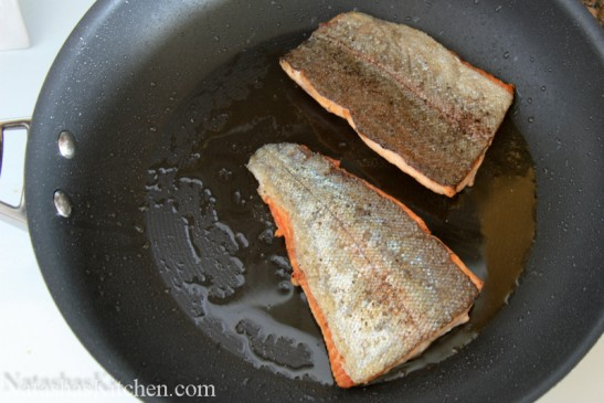 Two trout fillets skin side up on a skillet