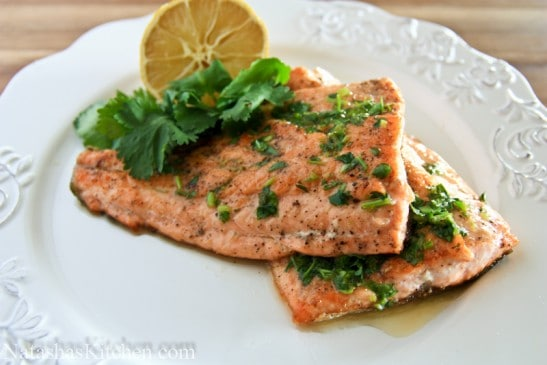 Two fillets of trout with parsley and lemon butter with half a lemon beside it
