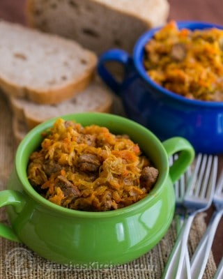 A green and blue bowl with braised cabbage with beef and bread in the background