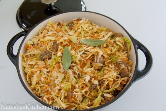 A dutch oven with braised cabbage with beef