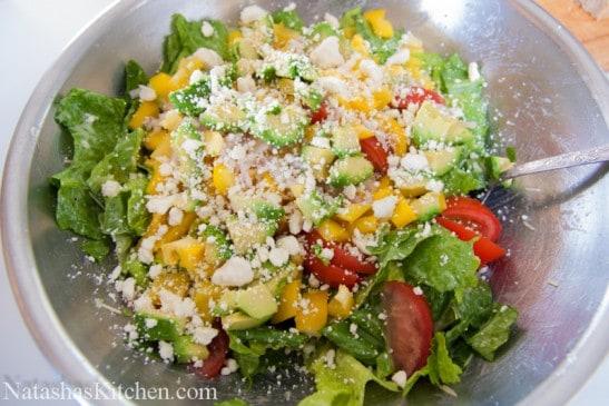 A large mixing bowl with avocado feta Caesar salad