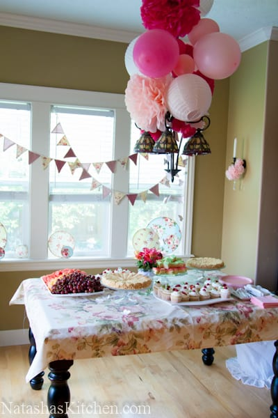 A room decorated for a baby shower with a sweets table
