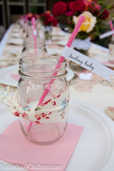 A mason jar wrapped with a floral ribbon, and a pink straw that says, darling baby