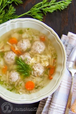A bowl of mom's meatball soup with a cloth napkin and spoon beside it