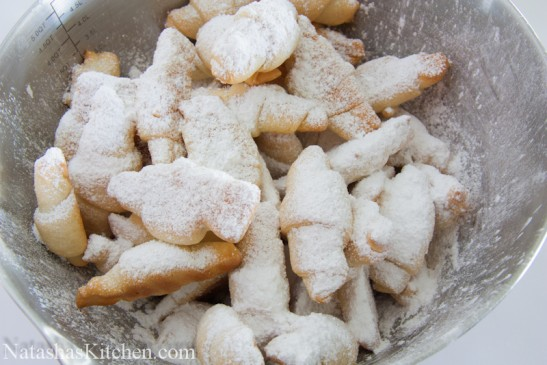 A bowl with rogaliki covered in powdered sugar