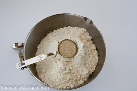 A bowl of flour with yeast being added to it