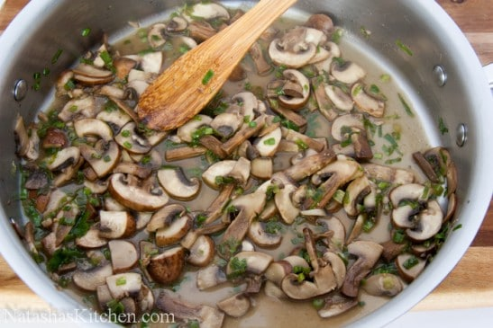 A pot with white wine, mushrooms, chives and butter