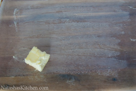 Parchment paper on a cutting board with butter rubbed on it