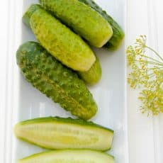 Pickles on a long tray with a piece of dill besides them
