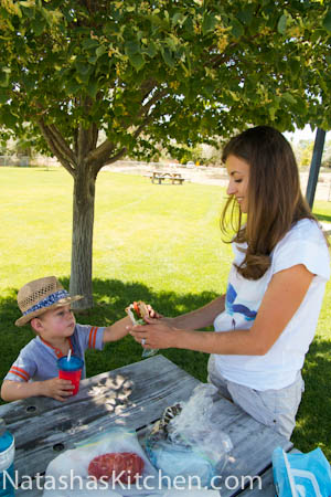 Natasha and her son at a picnic table and she is handing him a snack