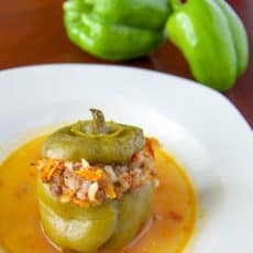 A plate of beef stuffed bell peppers with two raw green peppers behind the plate