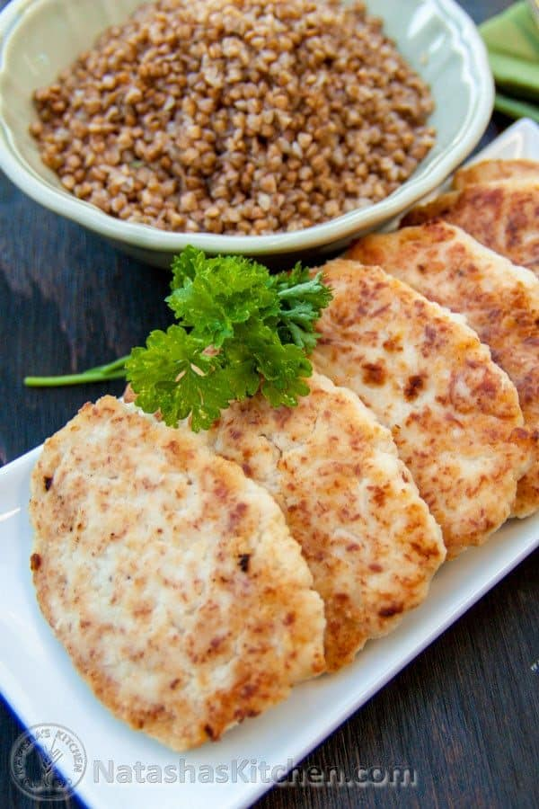 A plate of chicken kotleti lined up in a row with a bowl of buckwheat behind it