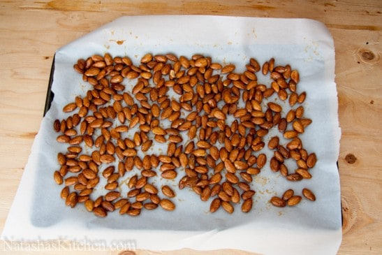 A baking pan lined with parchment paper with almonds being spread on it