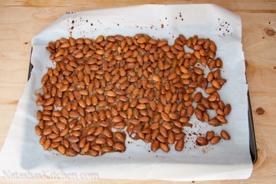 Honey glazed almonds on a baking pan lined with parchment paper