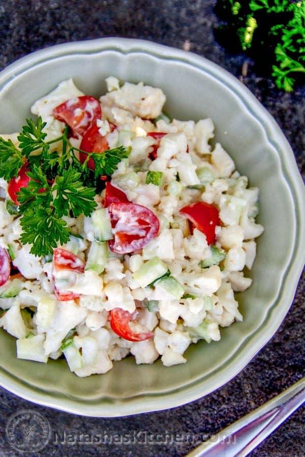 A bowl do cauliflower, cucumber and tomato salad