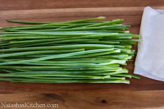 Green onion stacked up on a cutting board