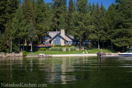 A large home next to a body of water surrounded by green trees