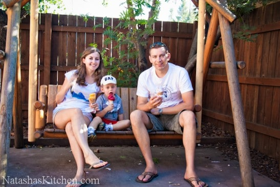 Natasha, her husband and son sitting in a rocking porch swing