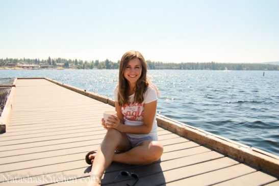 A woman sitting on a dock next to a body of water