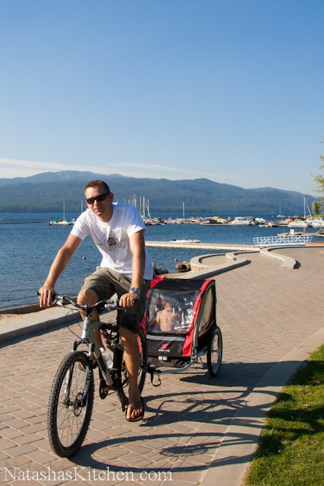 A man riding a bicycle next to a body of water