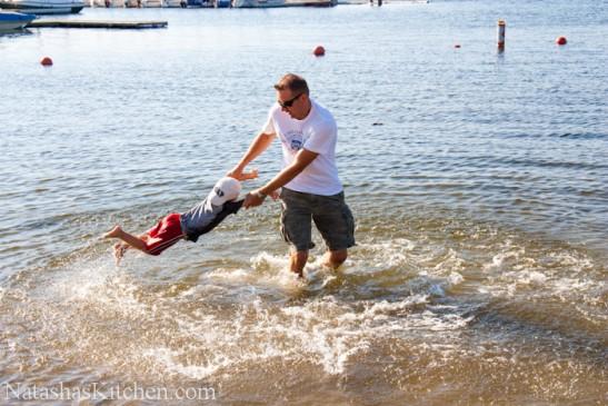 A man swinging a boy around at the beach
