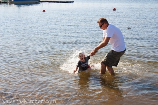 A man holding a little boys hand while he runs through the water and gets wet