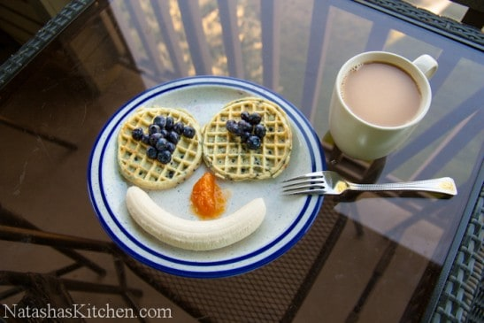 A plate of two waffles and bananas arranged into a smile and a cup of coffee