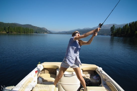Natasha standing in a boat and throwing in a fishing pole