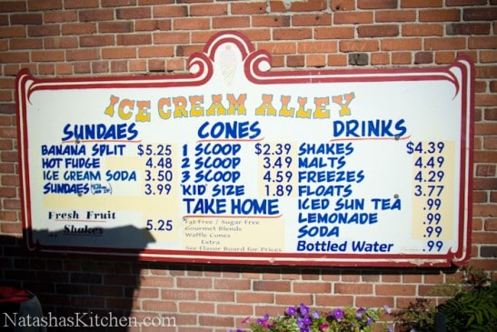 A sign in front of a brick building that says ice cream alley