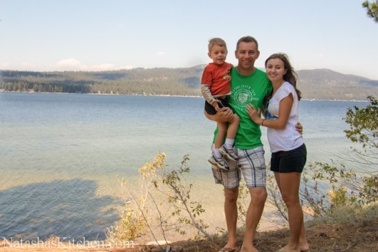 Natasha, her husband and her son standing next to a body of water
