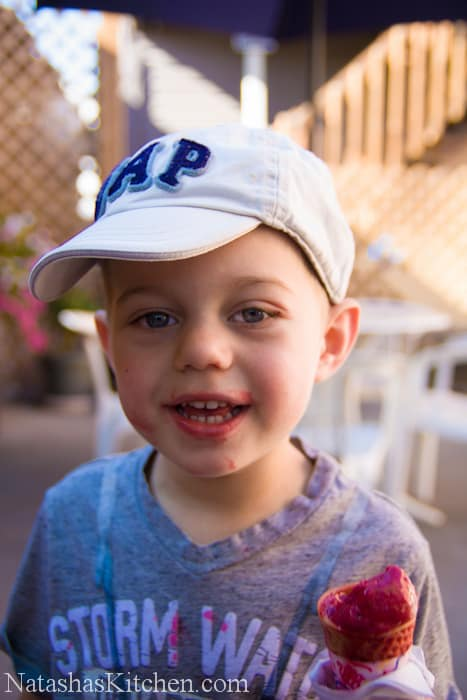 A little boy in a baseball cap with ice cream dripping down his chin