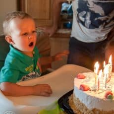 A little boy sitting in a high chair with a birthday cake in front of him