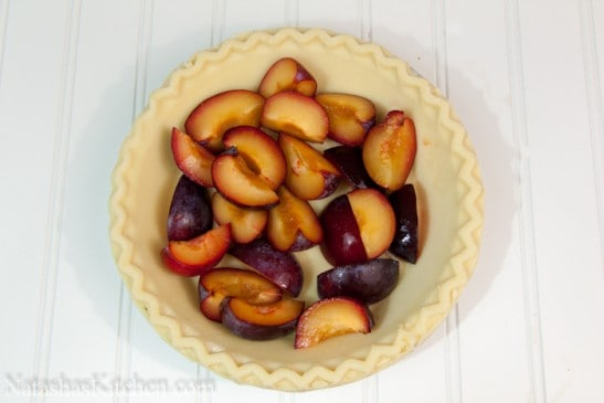 A pie crust filled with cut and pitted plums