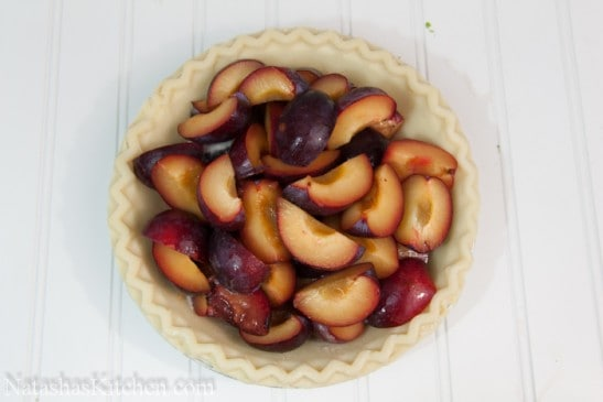 A pie crust filled with plums