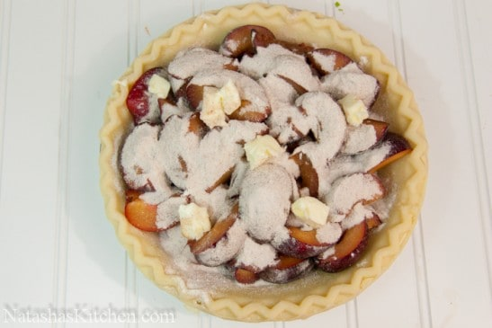 A pie crust filled with butter, plums and sugar
