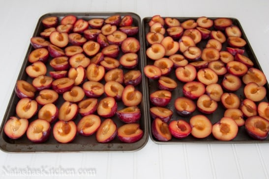 Two baking pans with halved plums spread out on it