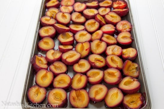 A baking pan with halved plums