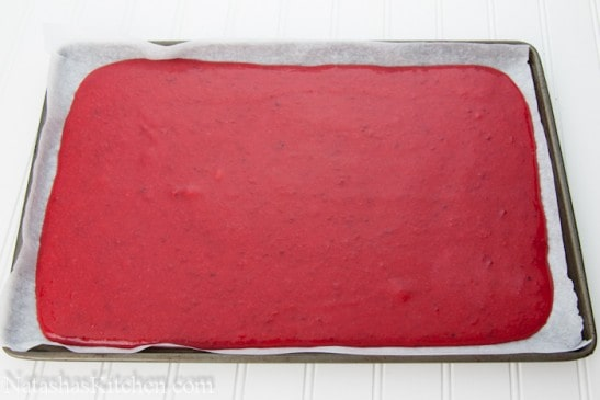 Pureed plum mixture spread out on a lined baking pan