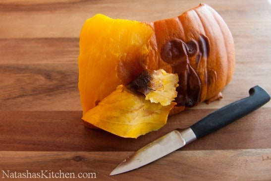 A piece of cooked pumpkin being peeled with a knife
