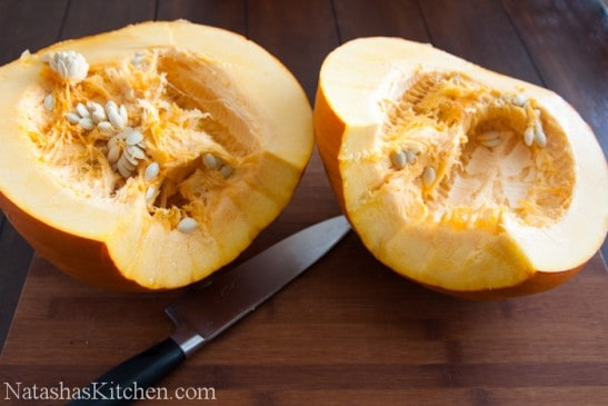 A halved pumpkin on a cutting board with the knife between the halves